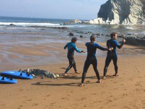 alumnos en clases de surf calentando en la arena de sopelana