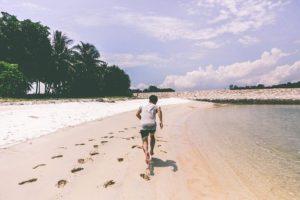persona corriendo por la playa un entrenamiento de resistencia recomendable para surf